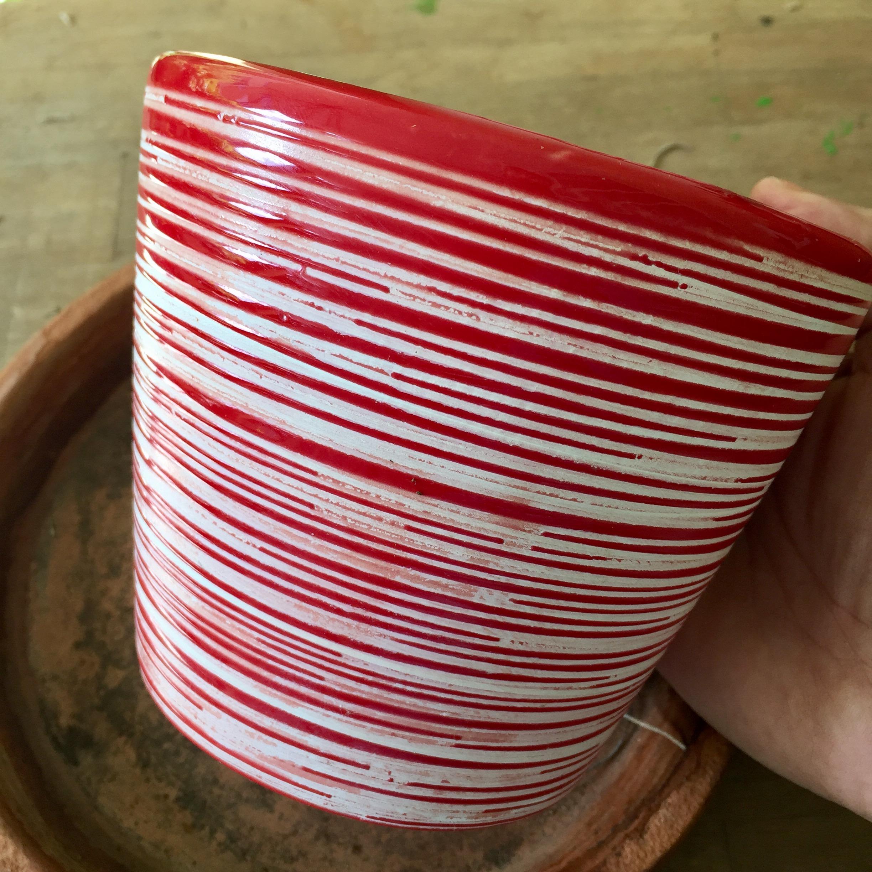Tiesto en cerámica sin drenaje. En vez de sembrar la planta directamente utiliza un tiesto plástico con agujeros para insertar en el tiesto decorativo.